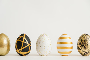 Easter golden decorated eggs stand in a row on white background. Minimal easter concept. Happy Easter card with copy space