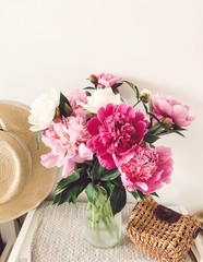 Stylish pink and white peonies in vase and trendy straw bag and hat on stylish white nightstand near bed. Hello spring. Happy Mothers day. Girly image