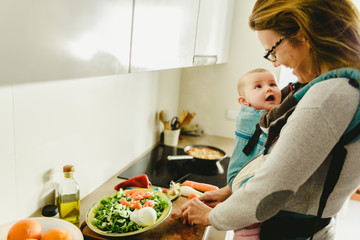 Smiling baby ported in baby carrier backpack looking at his mother while she cooks, concept of family conciliation Wall mural