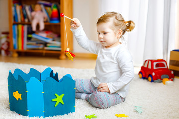 Adorable cute toddler girl playing with wooden fishing game at home or nursery. Happy healthy child training memory grabing with fishing rod . Development and coordination step and education of kid.