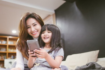 Portrait Happy Daughter playing smartphone with her mother