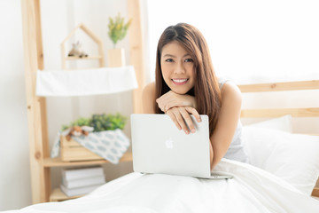 Happy young Asian woman working with a laptop in the bedroom