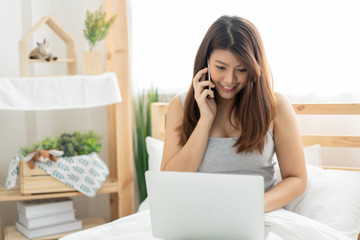 Happy young Asian woman using phone and working with a laptop in the bedroom