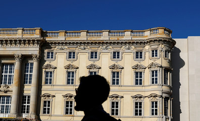 A man is silhouetted against a finished facade at the construction site of the Berliner Schloss (Berlin City Palace) - Humboldtforum in Berlin