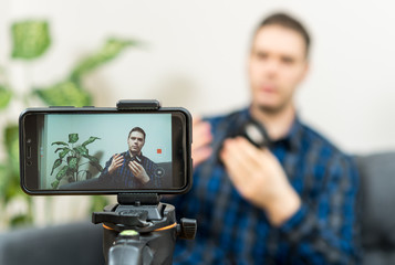 Man making video blog about photo camera lenses.