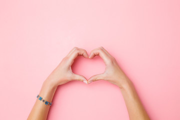 Heart shape created from young woman's hands on pastel pink background. Love and happiness concept. Empty place for emotional, sentimental text, quote or sayings. Closeup. Top view. Wall mural