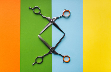 Metal scissor and thinning scissor of hairdresser on the background of pastel paper in the form of...