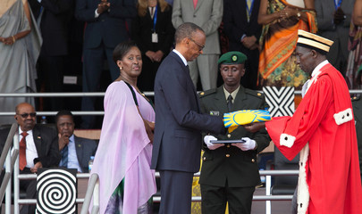 Rwanda's newly inaugurated President Paul Kagame receives the National flag from Chief Justice Sam Rugege next to First Lady Jeannette Kagame after taking the oath of office during his swearing-in ceremony at Amahoro stadium in Kigali
