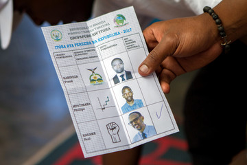 A polling staff member counts ballots at a polling centre in Kigali