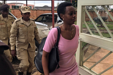 Diane Shima Rwigara, a prominent critic of Rwanda's president Paul Kagame, is escorted by police officers into a courtroom in Kigali