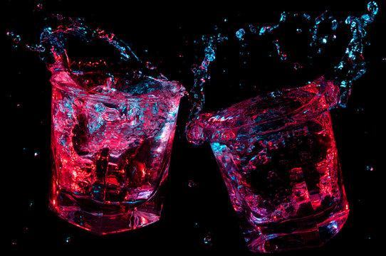 Rocks glasses toasting and splashing glowing liquid isolated on a black background
