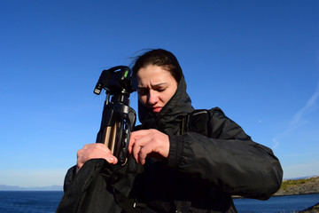 The girl on the background of the blue sea and sky holds a tripod for the camera. Photograph in windy weather by the sea.