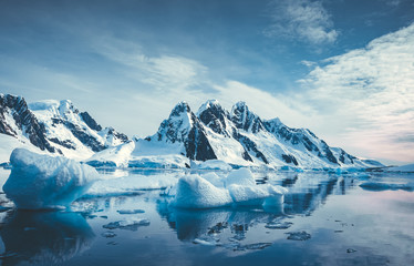 Papiers peints Antarctique Blue Ice covered mountains in south polar ocean. Winter Antarctic landscape. The mount's reflection in the crystal clear water. The cloudy sky over the massive rock glacier. Travel wild nature