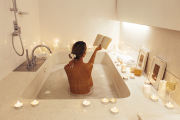Woman relaxing in bath with candles