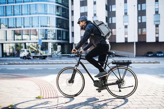 Male courier with bicycle delivering packages in city. Copy space.