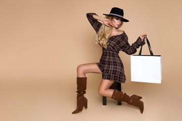 Fashion Model girl full length portrait isolated on beige background. Beauty stylish blonde woman posing in fashionable clothes in studio. Casual style, beauty accessories,hat and handbag Wall mural