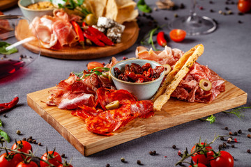 Italian food. Assortment of appetizers for a large company in a restaurant. Different types of smoked meat, sausages and cheeses. a glass of cool wine.