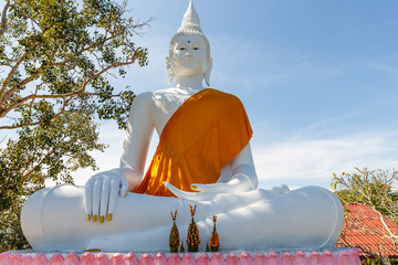 white statue of Buddha sitting in the lotus position, with an orange cape Laos Luang Prabang Province