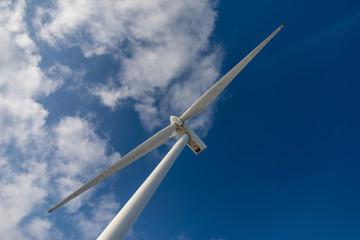 Vue des élices d'une éolienne sur fond de ciel bleu en contre-plongée