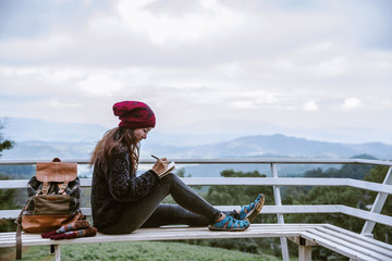 The girl is sitting relaxing at the natural mountain viewpoint and writing a record of her winter travel. smiled happy writing a diary.