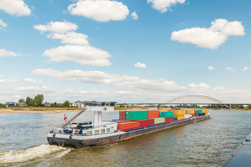 Container vessel passing the city of Nijmegen on the Dutch river Waal