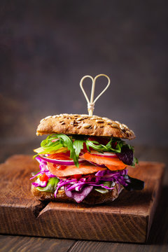 Sandwich with cereals bread and smoked fish on chopping board. Dark wood background.