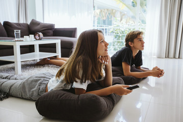 Teenagers watching tv while sitting on couch