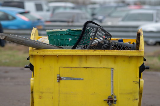 close up of yellow dumpster bin containing assorted plastic waste for recycling