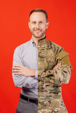 Young soldier in military wear keeping arms crossed and smiling  on red background.