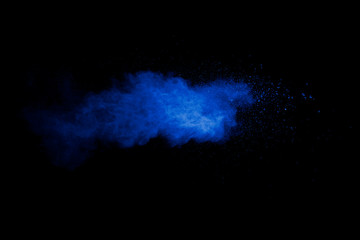 Abstract art blue powder on black background.