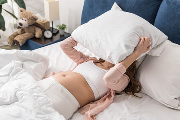 Pregnant woman trying to sleep while lying in bed