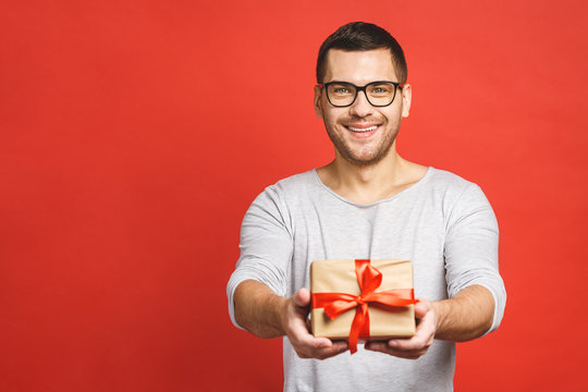 Happy holiday, my congredulations! Portrait of an attractive casual man giving present box and looking at camera isolated over red background.