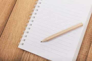 Open Notebook (Lined paper) with a pencil on wooden background
