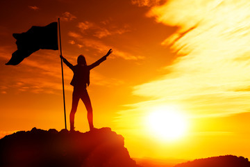 Silhouette of a girl with a flag on top of the mountain at sunset, the evening sky. goal achievement, success.