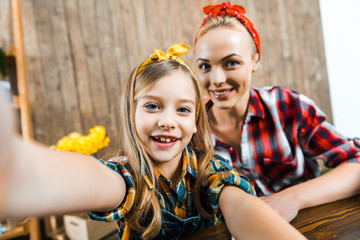 selective focus of cheerful kid taking selfie with beautiful mother