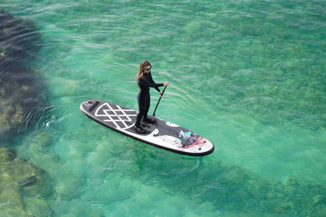 Woman Paddling on SUP board in a blue sea.