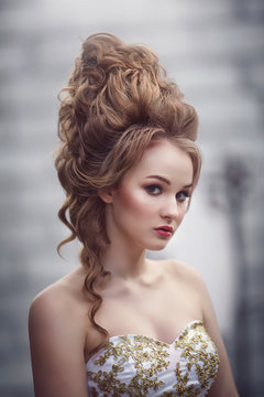 Beautiful woman in an ancient medieval dress, with a high complex historical hairstyle near the walls of the castle.