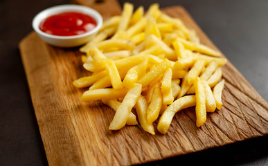 French fries with ketchup on a cutting board, background is concrete
