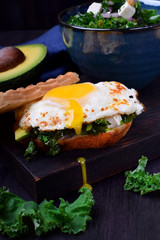 Sandwich with fried egg with liquid yolk and kale cabbage against the dark background