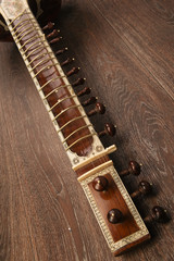 Close-up of a fingerboard Indian musical instrument sitar lying on a wooden floor