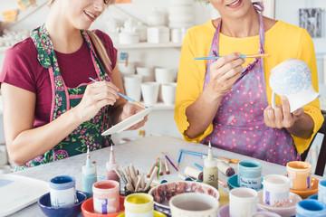 Frauen bemalen Geschirr mit Pinsel und Farben