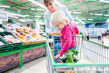 Frau fährt ihr Kind im Einkaufswagen im Supermarkt