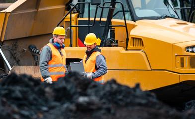 Arbeiter im Tagebau schauen auf einen Plan