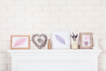 White fireplace with photo frames and lavender flowers in vase