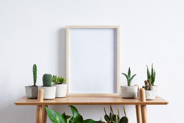 Stylish room interior with mock up photo frame on the brown bamboo shelf with beautiful plants in differents hipster and design pots. White walls. Modern and floral concept of shelfs.