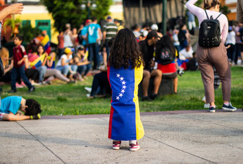 Venezuelan flag wrapped around young little girl at protest against Nicolas Maduro