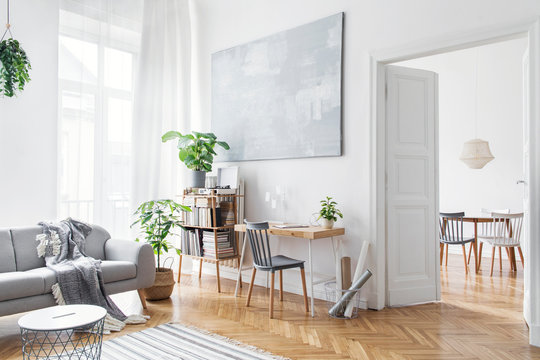 Stylish scandinavian open space with design furniture, plants, bamboo bookstand and wooden desk. Brown wooden parquet. Abstract painting. Modern decor of bright room next to dining room.