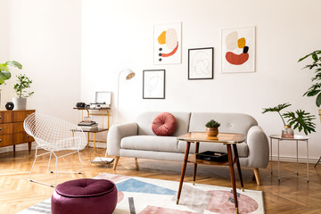 Minimal retro interior design of living room with grey couch, design armchair vintage coffee table, lamp and stylish decorations. Bright room, brwon wooden parquet and poster gallery on the wall.