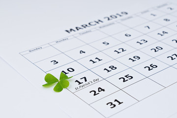 Closeup view of paper calendar sheet with selected date March 17 and clover leaf. Happy St Patrick's day is Public holiday Ireland concept. Selective focus, shallow DOF
