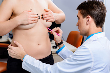 Doctor drawing marks on patient's breast for cosmetic surgery operation against gray background, closeup